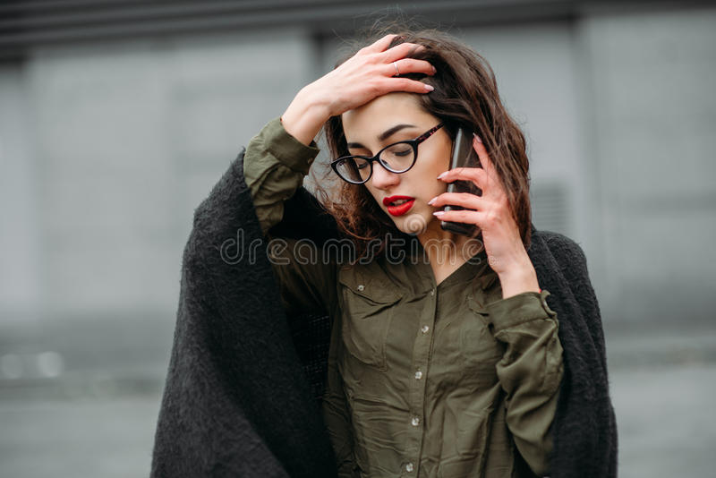 Fashion consept: beatiful young girl with long hair, glasses, red lips standing near modern wall wearing in green suit and grey je stock images