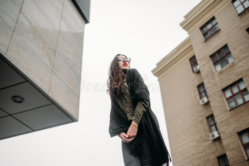Fashion consept: beatiful young girl with long hair, glasses, red lips standing near modern wall wearing in green suit and grey je royalty free stock photos