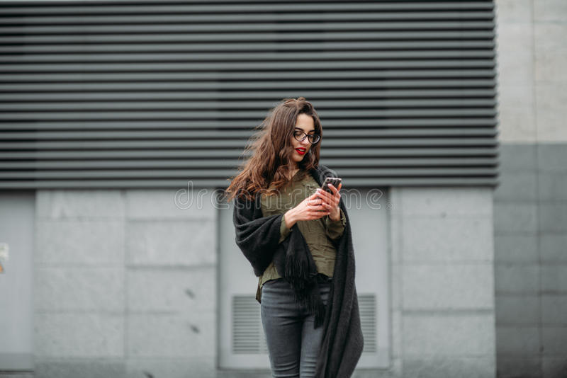 Fashion consept: beatiful young girl with long hair, glasses, red lips standing near modern wall wearing in green suit and grey je stock photography