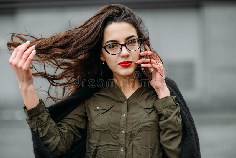 Fashion consept: beatiful young girl with long hair, glasses, red lips standing near modern wall wearing in green suit and grey je royalty free stock images