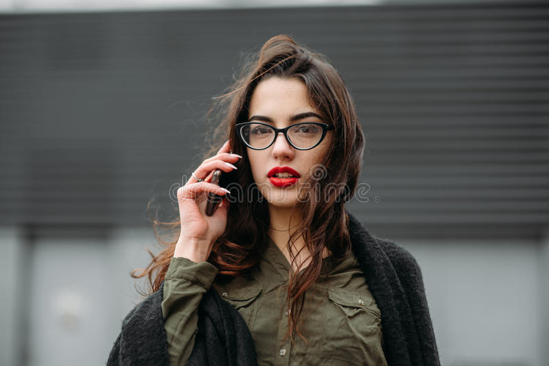Fashion consept: beatiful young girl with long hair, glasses, red lips standing near modern wall wearing in green suit and grey je stock photos