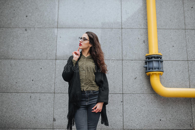 Fashion consept: beatiful young girl with long hair, glasses, red lips standing near modern wall wearing in green suit and grey je royalty free stock photo