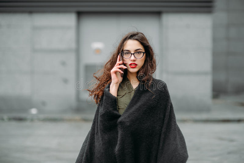 Fashion consept: beatiful young girl with long hair, glasses, red lips standing near modern wall wearing in green suit and grey je stock image