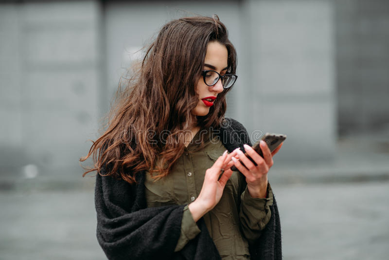 Fashion consept: beatiful young girl with long hair, glasses, red lips standing near modern wall wearing in green suit and grey je royalty free stock image