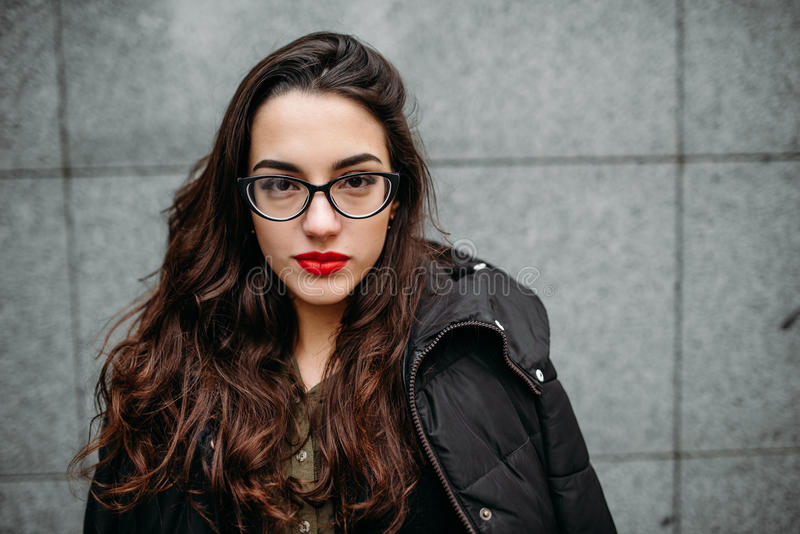 Fashion consept: beatiful young girl with long hair, glasses, red lips standing near modern wall wearing in green suit and grey je royalty free stock photography