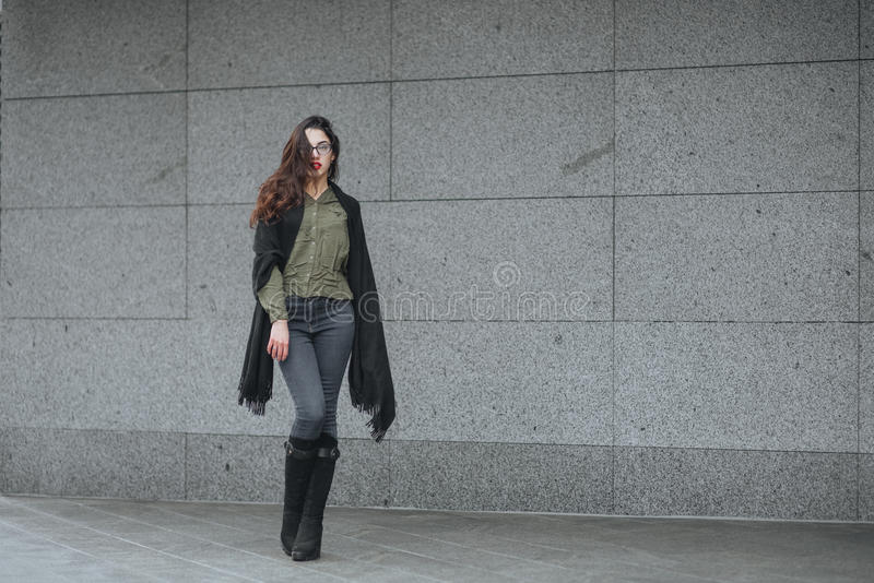 Fashion consept: beatiful young girl with long hair, glasses, red lips standing near modern wall wearing in green suit and grey je stock photo
