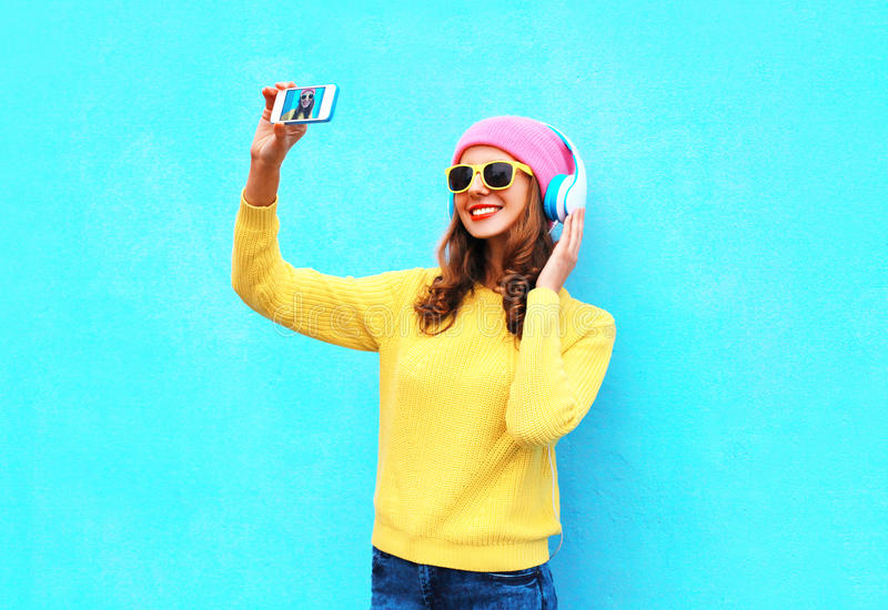 Fashion cool girl in headphones listening music taking photo makes self portrait on smartphone wearing a colorful clothes. Over blue background royalty free stock image