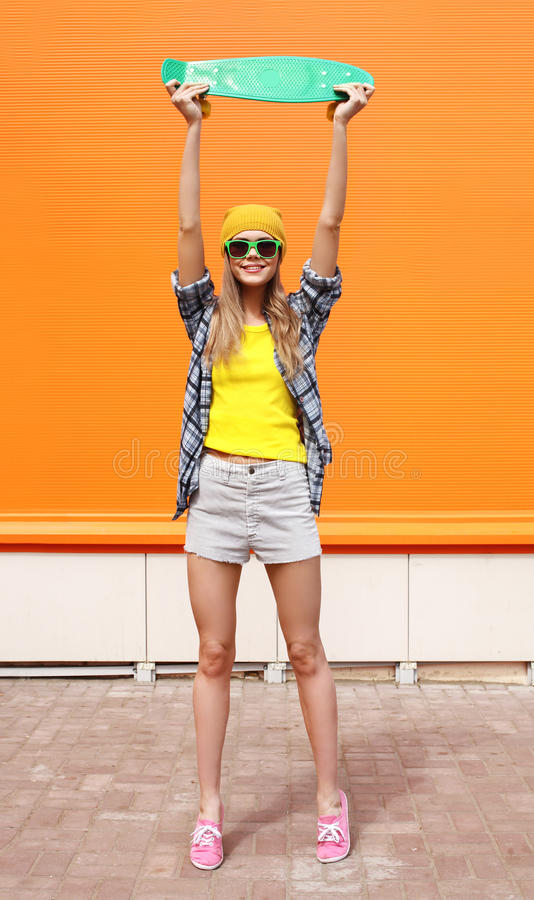 Fashion cool girl in sunglasses and colorful clothes, skateboard. Fashion cool girl in sunglasses and colorful clothes with skateboard having fun against the royalty free stock photos