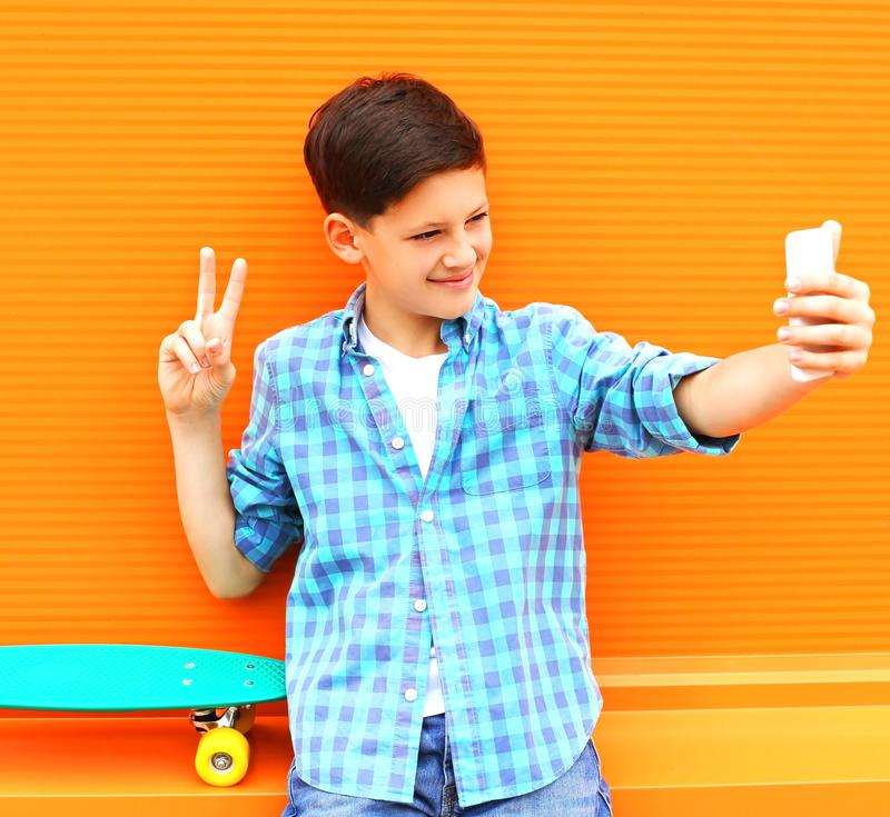 Fashion cool teenager boy is taking picture self portrait. On a smartphone royalty free stock photo