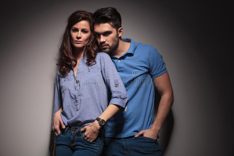 Fashion couple leaning embraced on a grey wall. Young fashion couple leaning embraced on a grey wall, both holding hand in pocket stock image