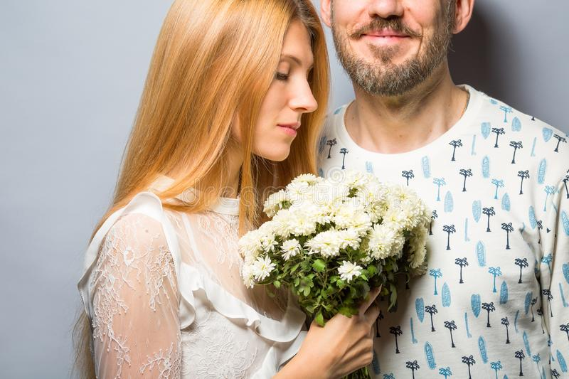 Fashion couple in love with a white bouquet of color in the stud stock images