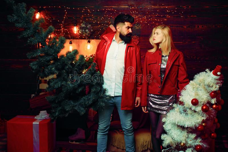 Fashion couple over Christmas tree lights background. Having a crazy day with friend. Expression and people concept. royalty free stock image