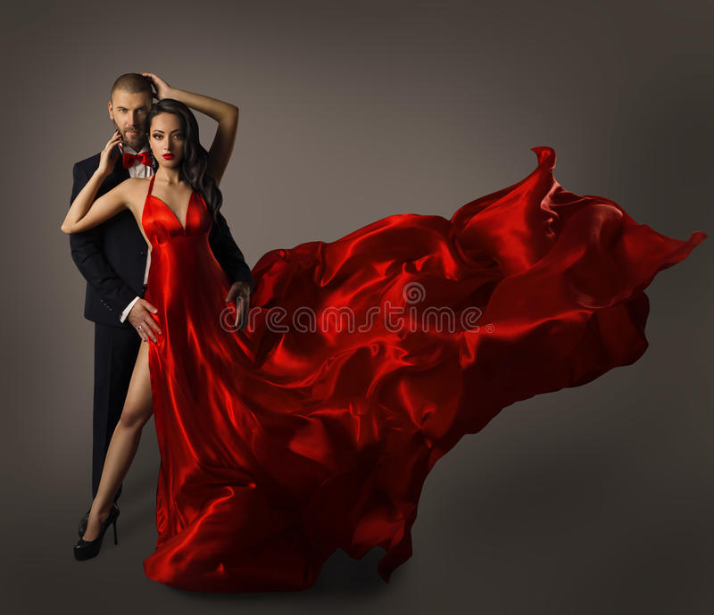 Fashion Couple Portrait, Woman Red Dress, Man in Suit, Long Cloth. Fashion Couple Portrait, Woman Red Dress, Man in Suit, Long Waving Cloth Flying over Gray