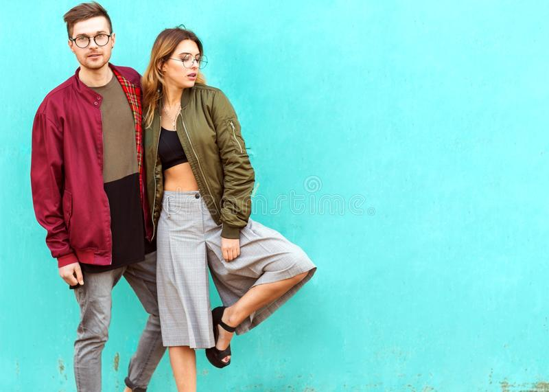 Fashion couple in their glasses with burgundy clothes posing on royalty free stock photos