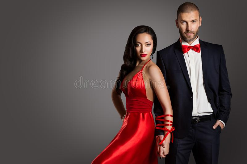 Fashion Couple, Woman and Man Arms Bounded by Ribbon, Red Dress Black Suit stock photo