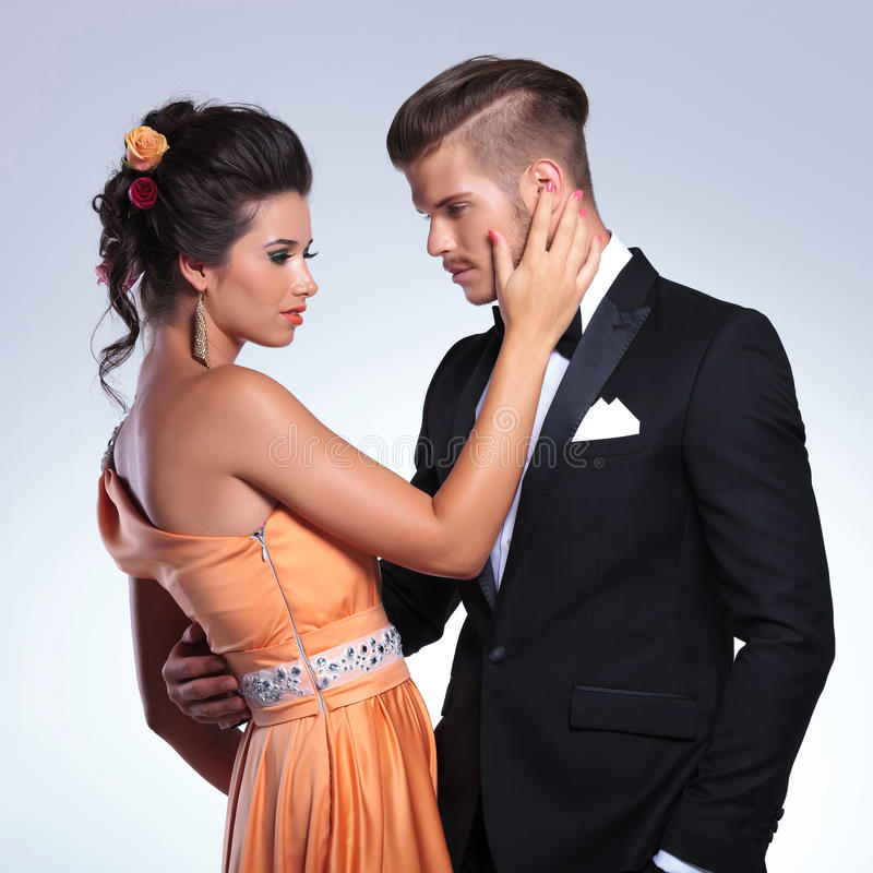 Fashion couple with woman touching man's face stock photography