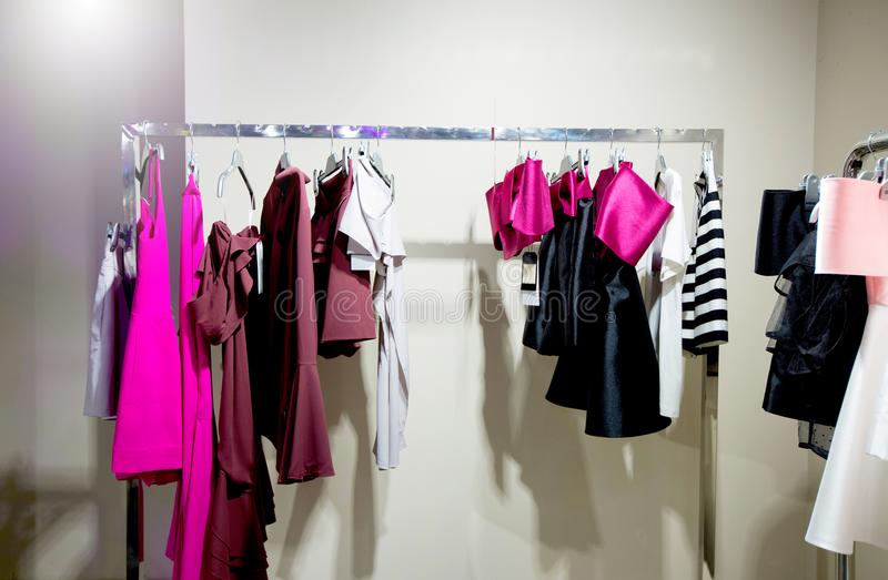 Fashion Design Clothes on Display rack in retail shop. New collection evening gown, casual, dress in window shopping on sale with stylist services in spring stock photos