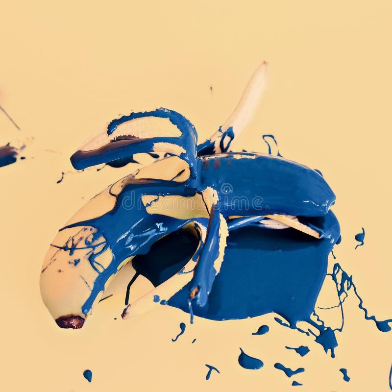 Fashion design photo banana with blue paint on yellow background stock photos