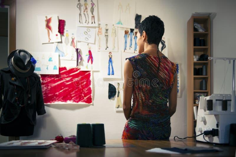Fashion designer contemplating drawings in studio royalty free stock photos