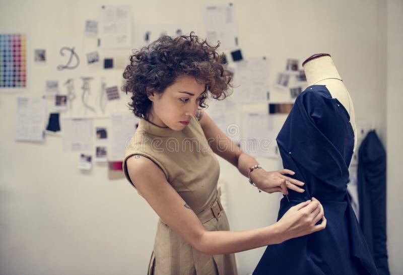 Fashion designer designing a black dress stock photos