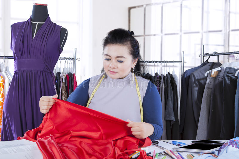 Fashion designer with fabric on workplace stock image