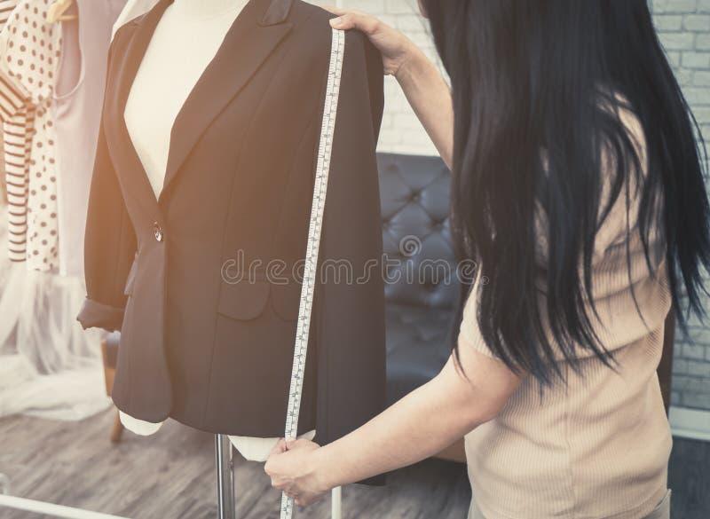 Fashion Designer hand measuring jacket length stock images