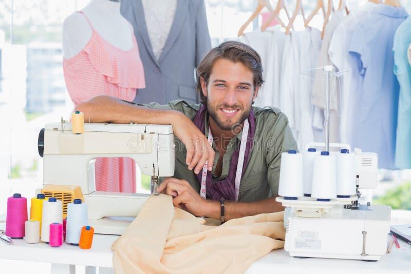 Fashion designer leaning on sewing machine royalty free stock photos
