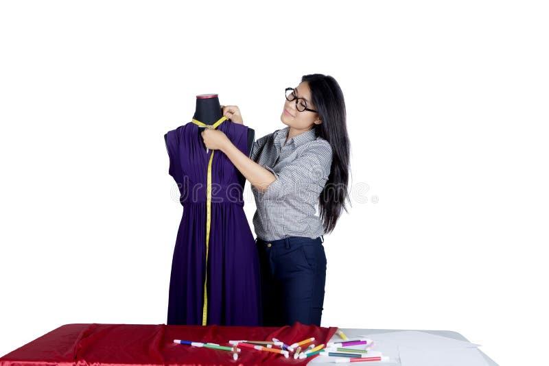 Fashion designer measure a clothes on studio stock image