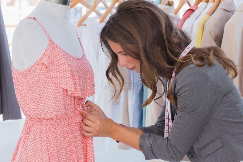 Fashion Designer Measuring Dress On A Mannequin Stock