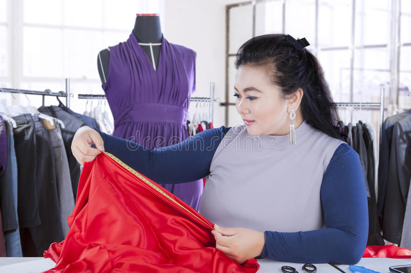 Fashion designer measuring fabric in the workplace royalty free stock image