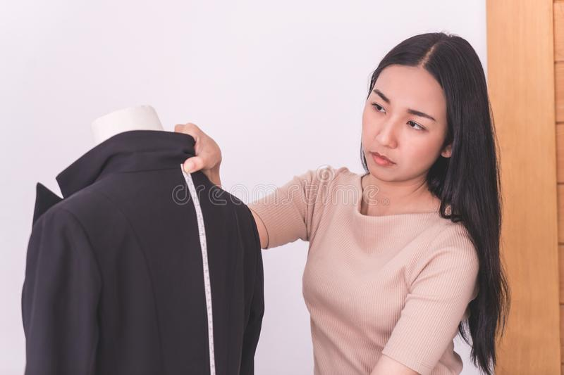 Fashion Designer is measuring jacket body with measuring tape royalty free stock images