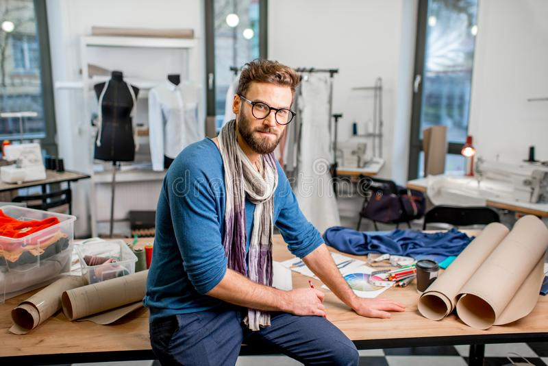 Fashion designer at the studio. Portrait of a handsome fashion designer sitting with paper sketches at the studio full of tailoring tools and clothes stock photography