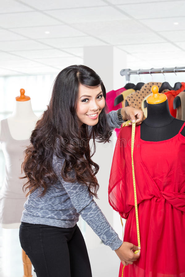 Fashion designer or Tailor working on a design or draft, she takes measure on a dressmakers dummy stock photos