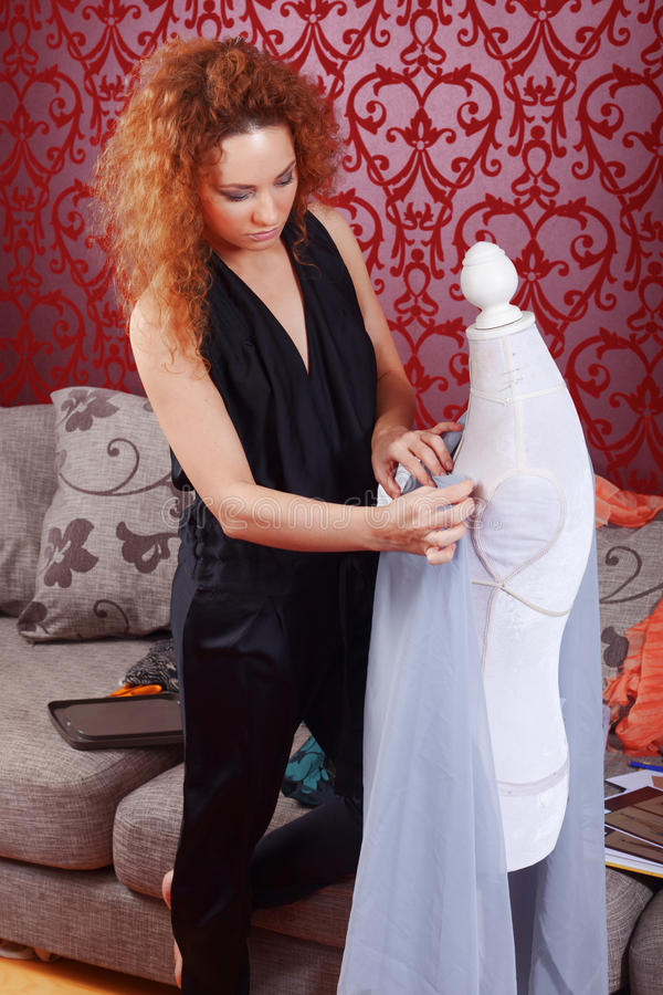 Fashion designer at work. Fashion designer is working on the new collection stock image