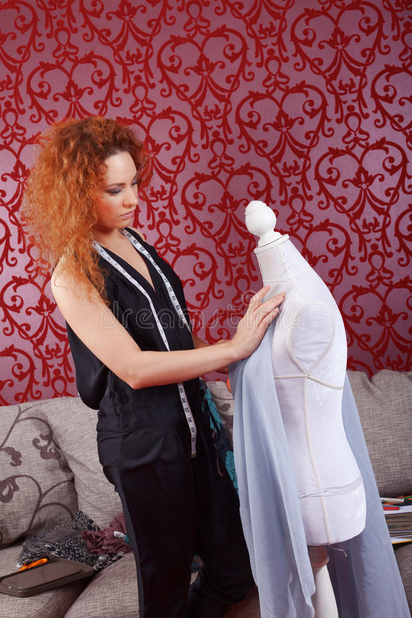 Fashion designer at work. Fashion designer is working on the new collection stock photography