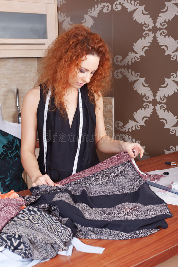Fashion designer at work. Fashion designer is working on the new collection stock photos