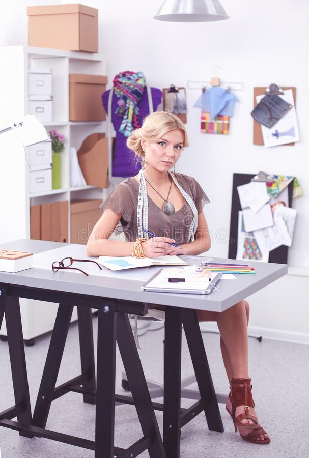 Fashion designer working on her designs in the studio stock images
