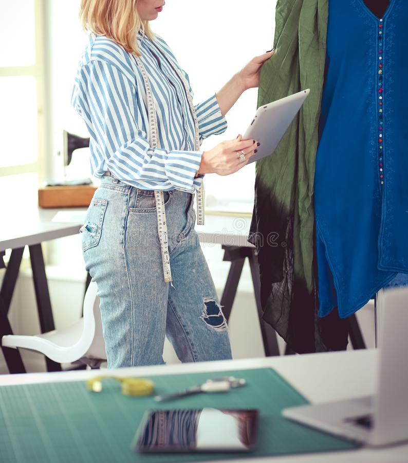Fashion designer working on her designs in the studio royalty free stock image