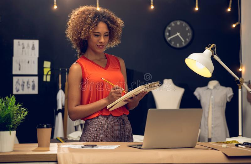 Fashion designer working on her atelier stock photography