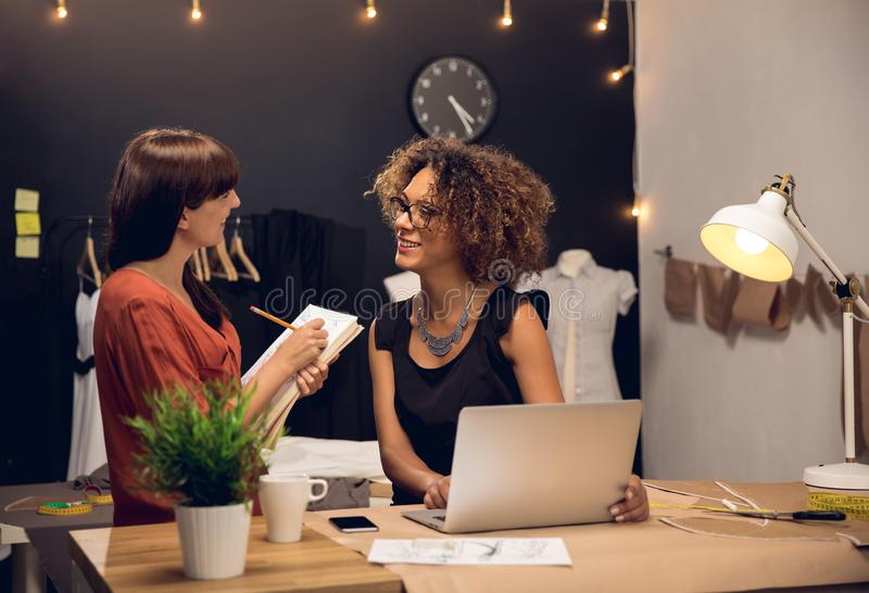 Fashion designers. Two young entrepreneur women, and fashion designer working on her atelier stock photos