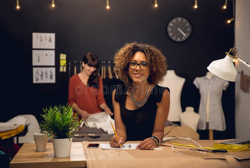 Fashion designers working together. Two young entrepreneur women, and fashion designer working on her atelier stock photo