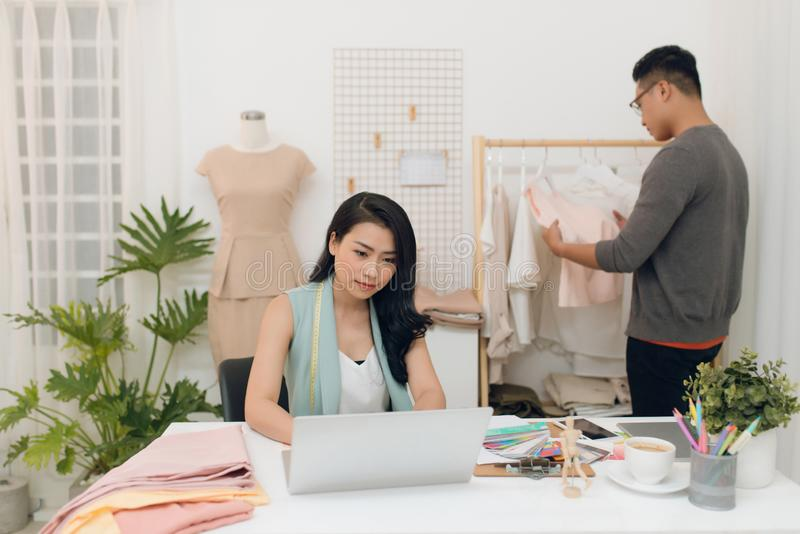 Fashion designers at work.  Handsome male designer choosing design while his colleague working with laptop royalty free stock images