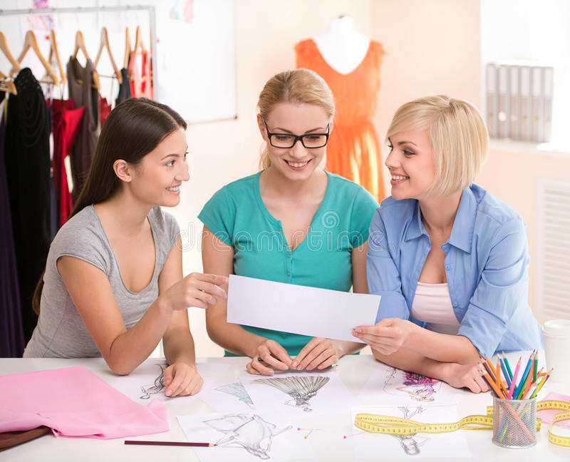 Fashion designers at work. Three cheerful young women working at. Fashion design studio stock image