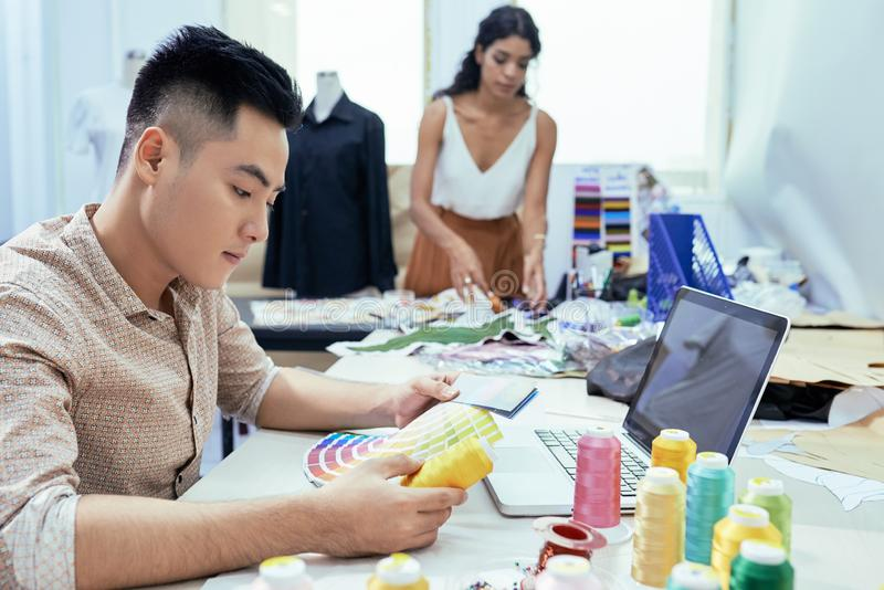 Fashion designers working in sewing workshop stock photography