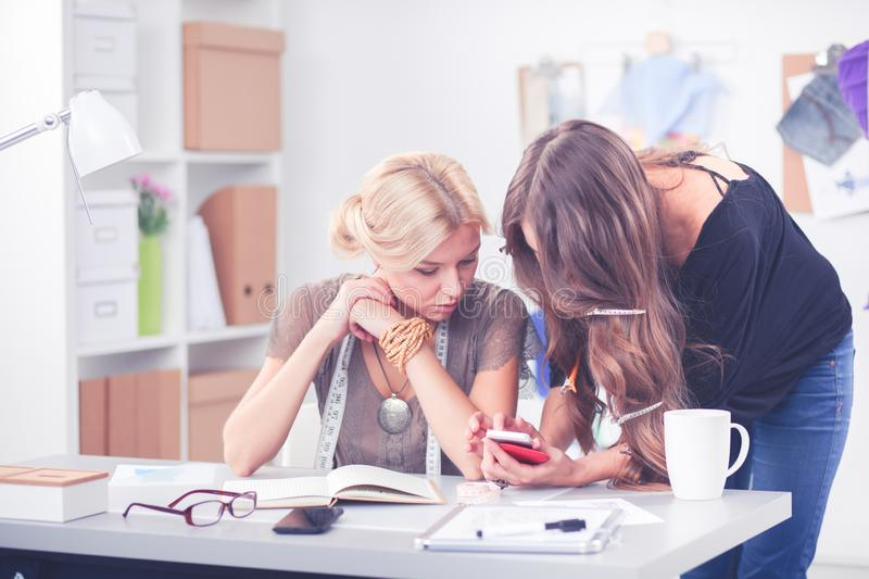 Fashion designers working in studio sitting on the desk royalty free stock photo
