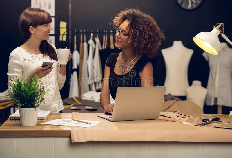 Fashion designers working together. Two young entrepreneur women, and fashion designer working on her atelier royalty free stock image