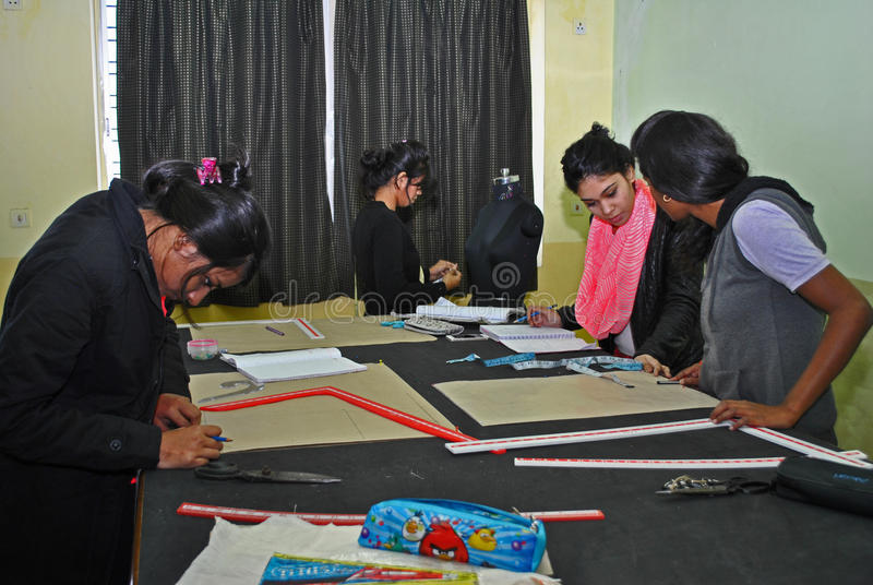 Fashion Designing. A group of young Indian girl is busy with designing garments in a workshop in India. Fashion industry is booming in India and a lot of job royalty free stock image