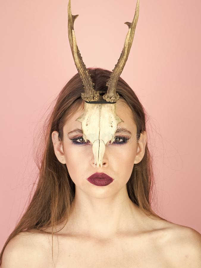 Fashion devil of mystic shaman girl with horns. Woman with makeup and antlers. Beauty look and cosmetics for skincare royalty free stock photo