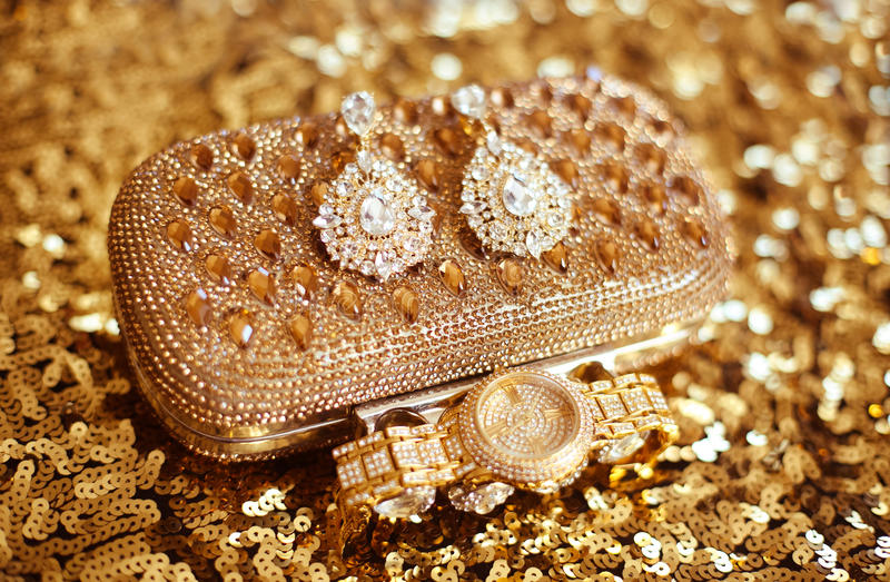 Fashion diamond earrings and golden wristwatch, womens accessories precious Gem Jewel Set on sequins sparkling sequined textile. stock photo