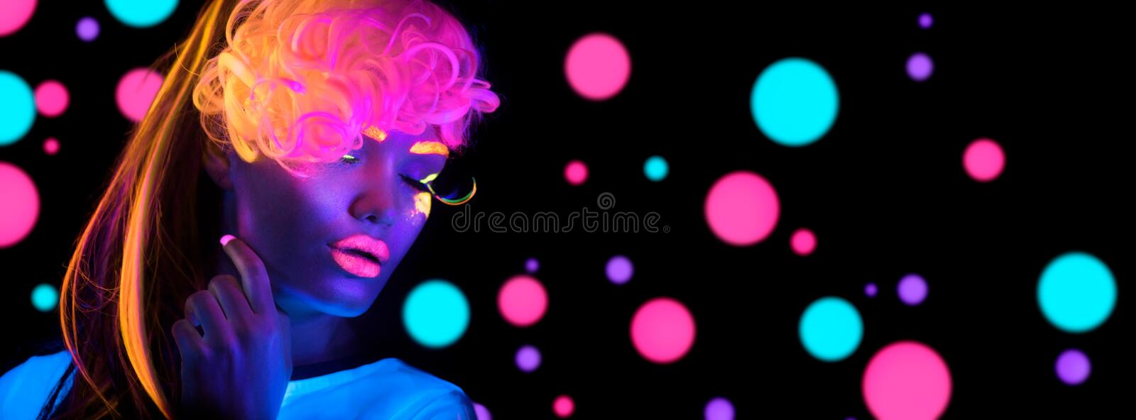 Fashion disco woman. Dancing model in neon light, portrait of beauty girl with fluorescent makeup stock photo